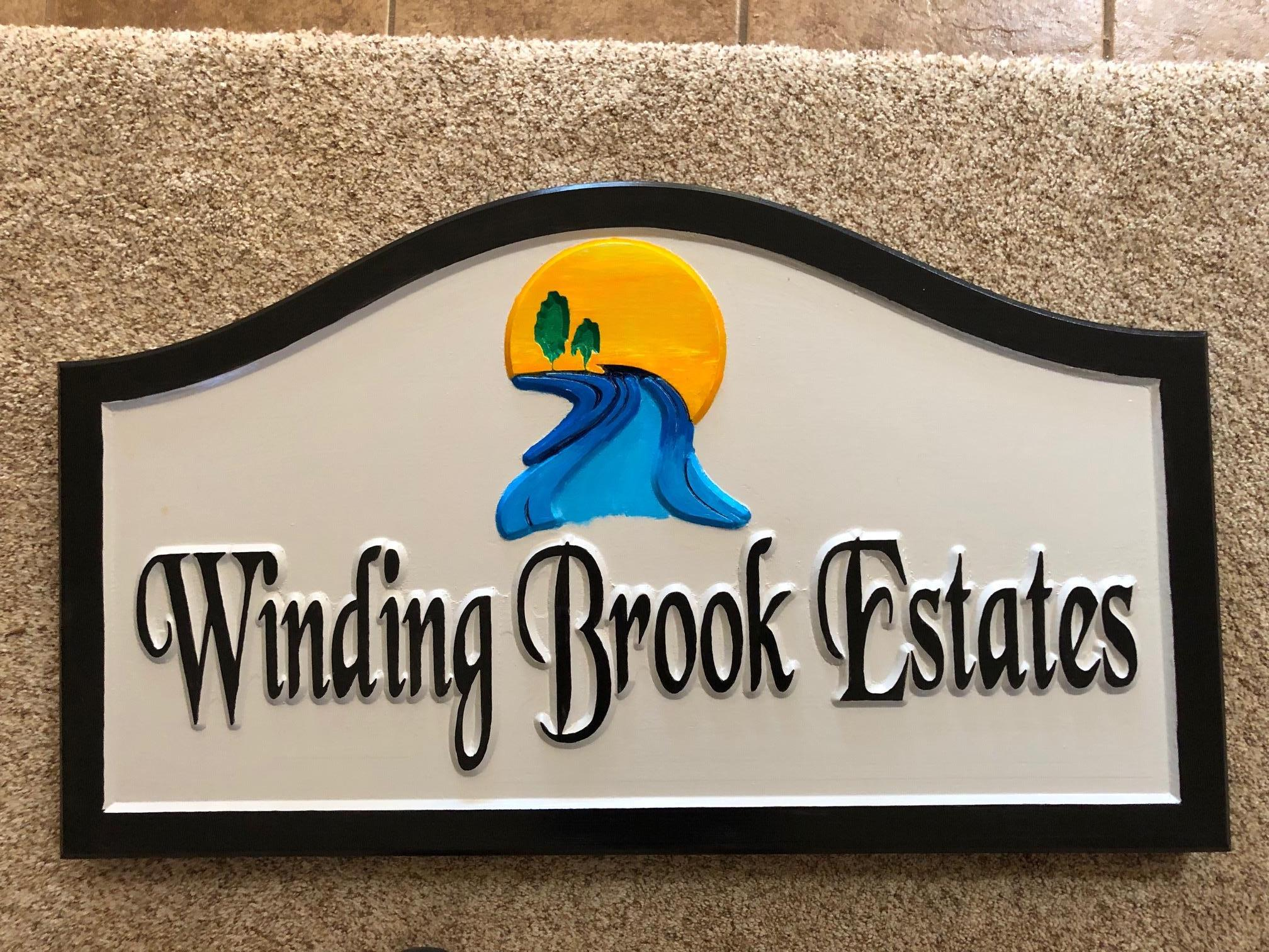 623  Windy Brook Estates community sign with graphic sun, tree and river