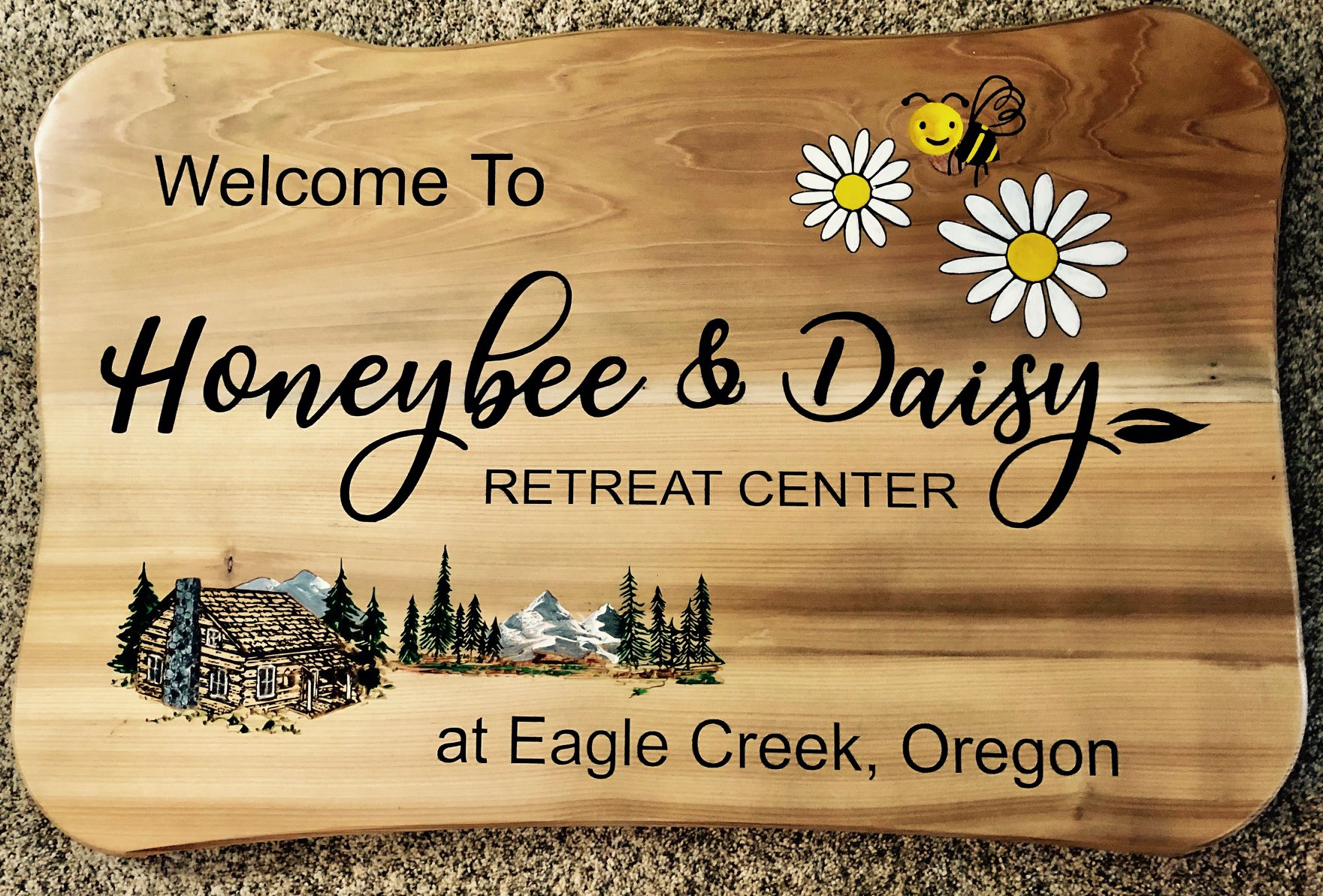 624  outdoor wooden sign for Honeybee & Daisy Oregon Retreat. Graphics for bee, daisies and rustic cabin in mountain scene